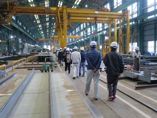 工場内に設置されている巨大な製作設備を見学中の様子